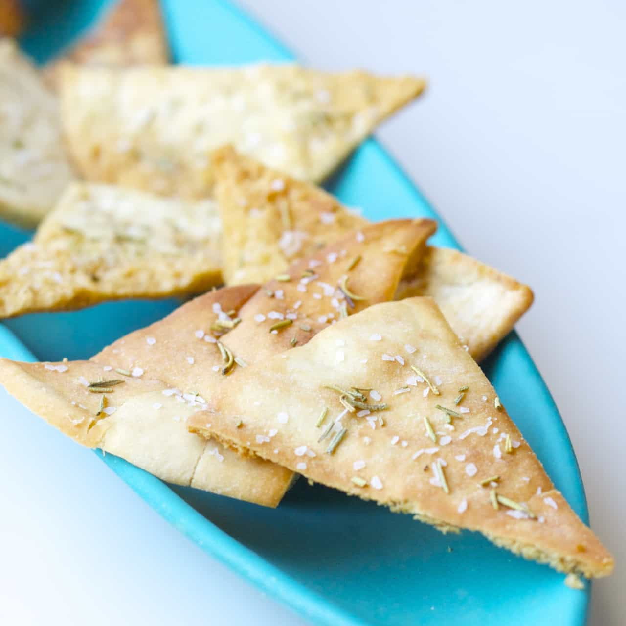 These homemade pita chips are seasoned with salt and rosemary and baked to crispy perfection. An easy snack to make at home!