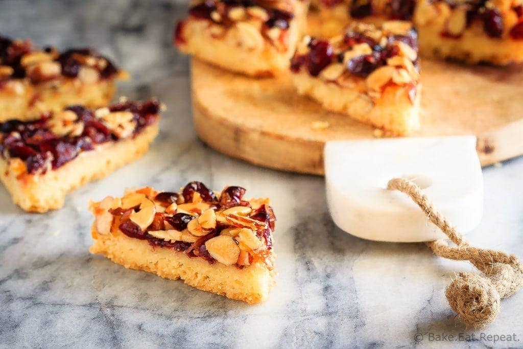 Glazed Cranberry Almond Bars - These glazed cranberry almond bars are the perfect addition to your Christmas cookie tray. Pretty, festive, and so easy to make, everyone will love them!