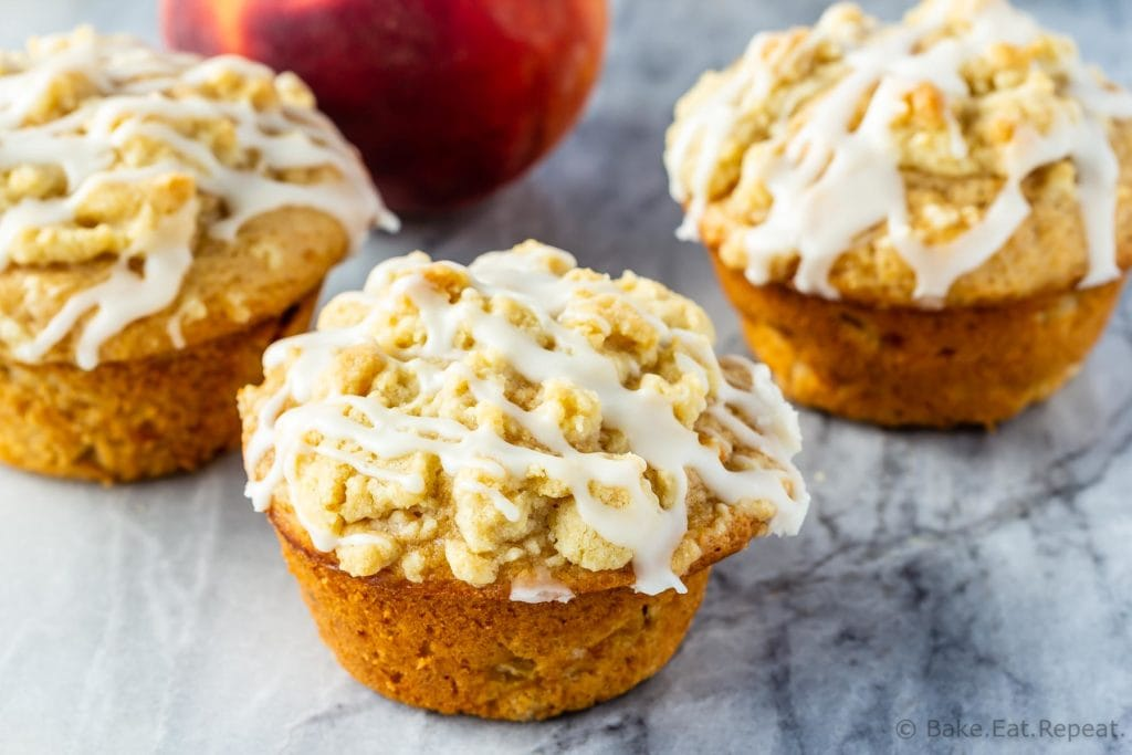 Fresh peach muffins with a crumb topping and a vanilla glaze