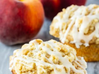 Peach muffins with a crumb topping and a vanilla glaze