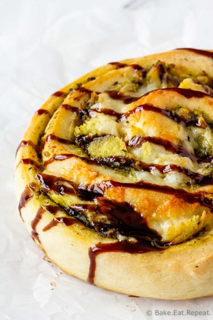 Easy to make pesto chicken pizza rolls drizzled with balsamic glaze.