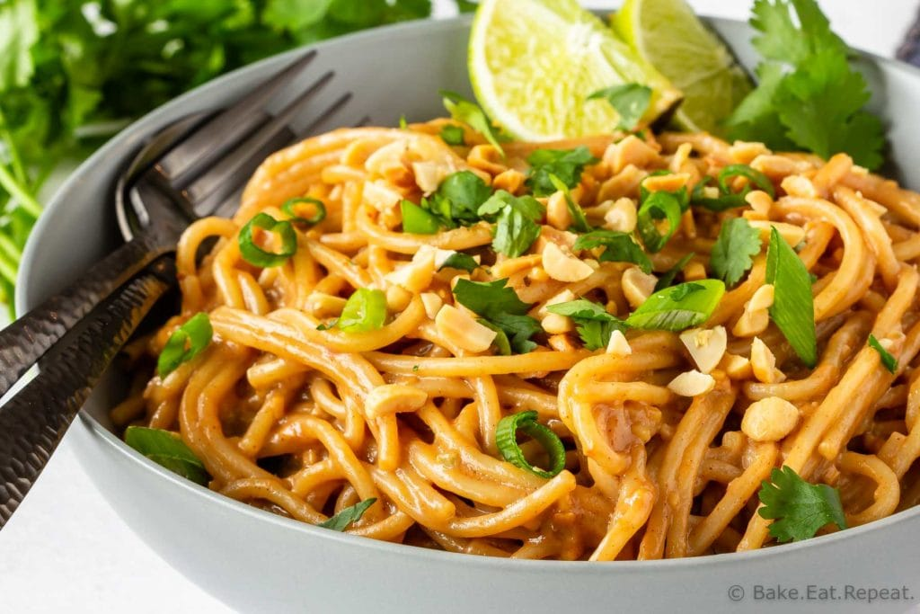 Homemade peanut pasta sauce on noodles with lime, green onions, and cilantro