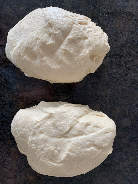 Two piece of bread dough ready to shape into loaves.