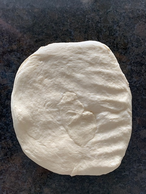 Bread dough pressed out into a thick rectangle to start shaping it into a loaf.