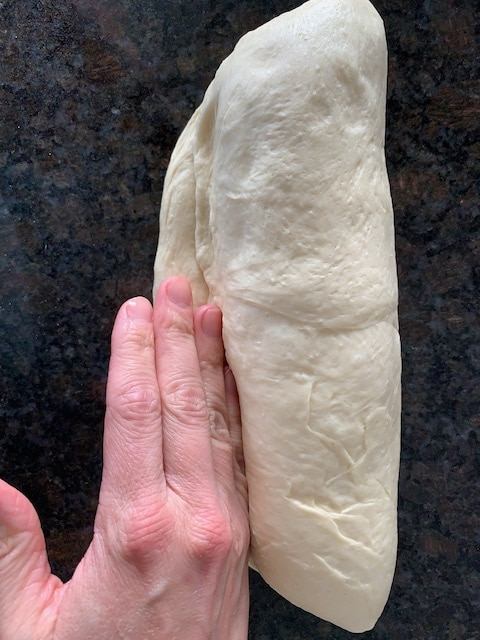 Shaping bread dough into a loaf, sealing the seam.