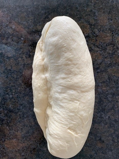 Shaping bread dough into a loaf.