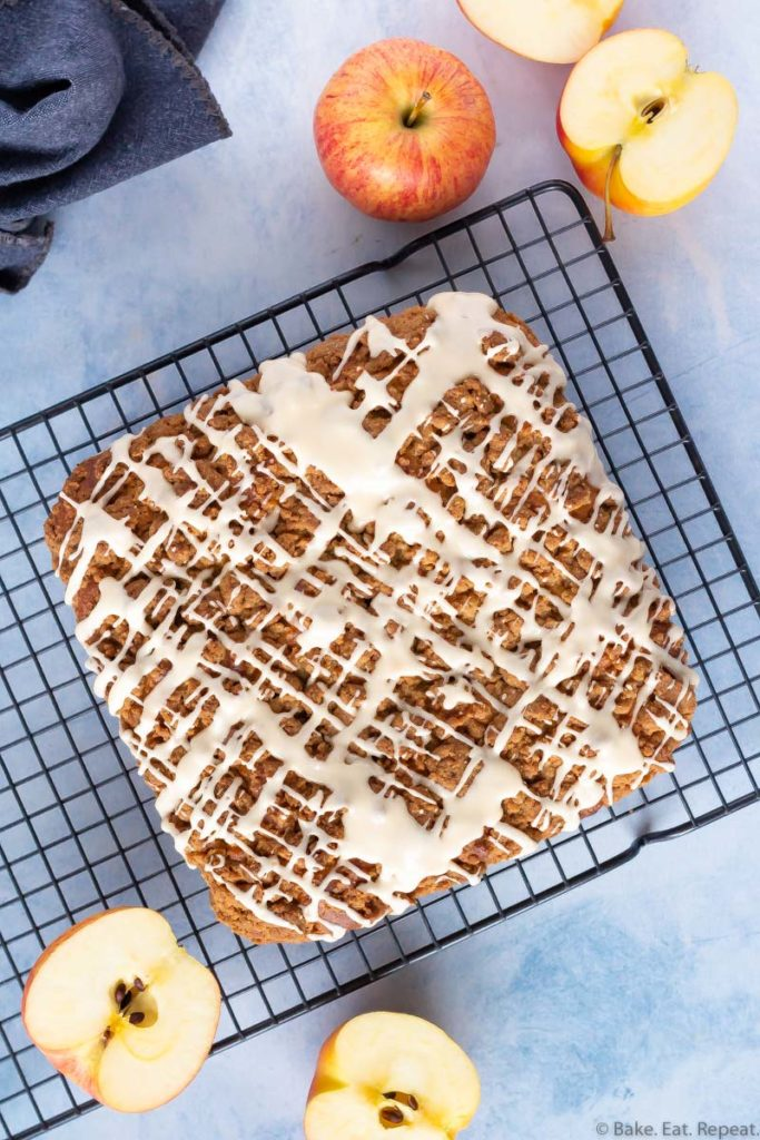 An apple coffee cake with a crumb topping and a salted caramel glaze on a cooling rack with apples.