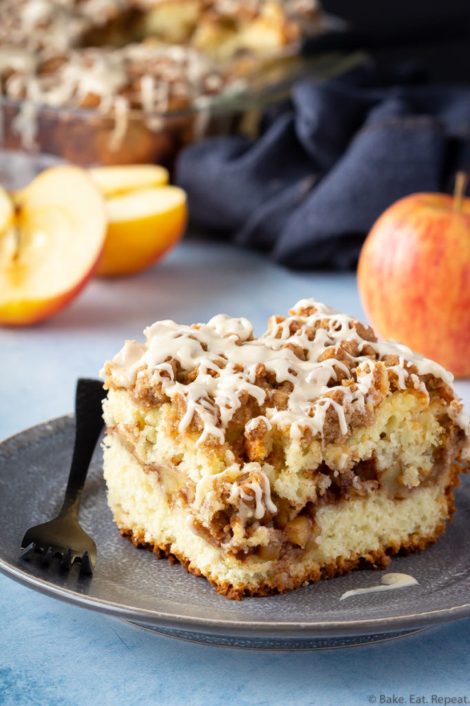 A piece of apple coffee cake on a plate with apples and the pan of coffee cake.