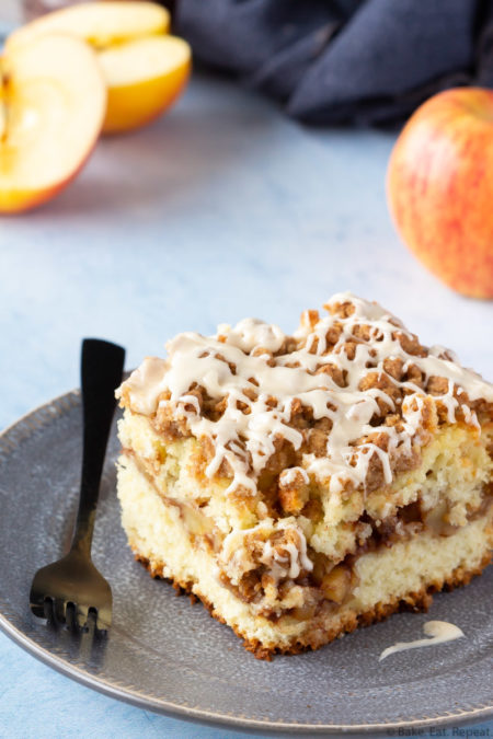Piece of apple cinnamon filled coffee cake with a crumb topping and a salted caramel glaze on a place with apples.