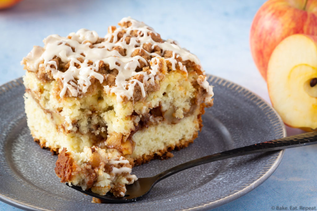 Easy cake filled with cinnamon apples and topped with a crumb topping and salted caramel glaze on a plate.