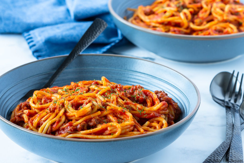 two bowls of spaghetti and meat sauce cooked in the Instant Pot.
