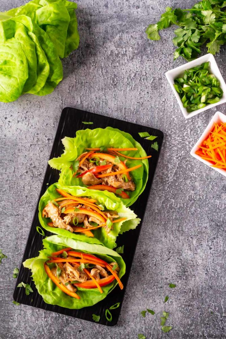 Hoisin chicken lettuce wraps on a platter with carrots, lettuce, cilantro and green onions.