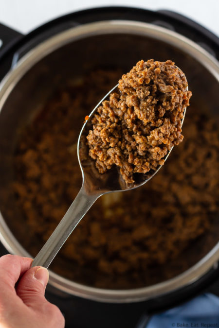 A spoonful of cooked taco meat held above the Instant Pot where it was cooked from frozen ground beef.