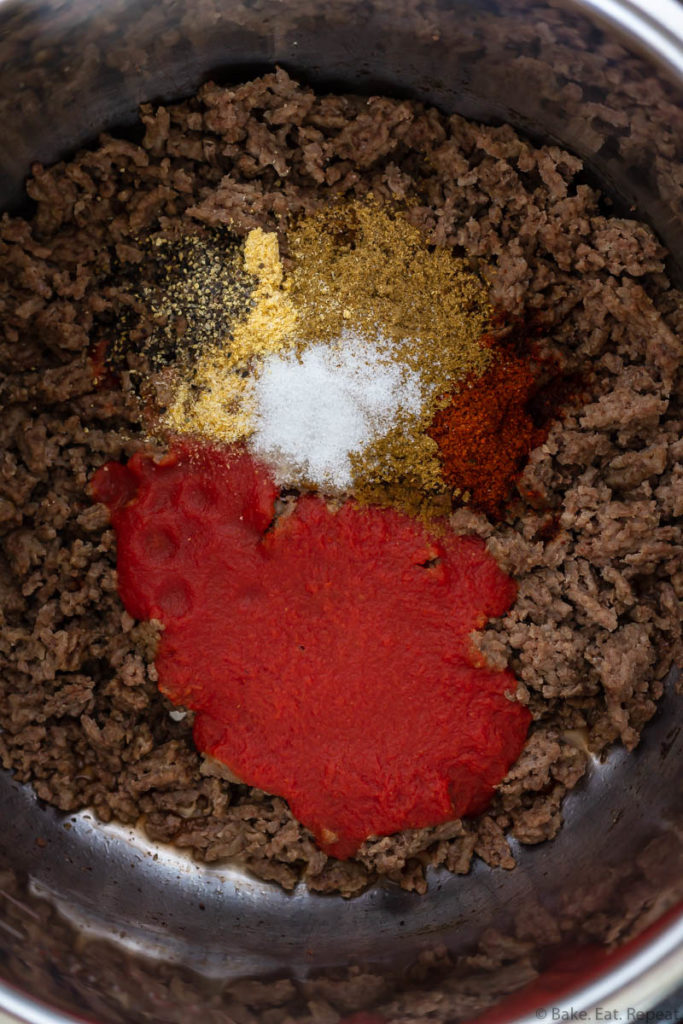 The ingredients for taco meat in the Instant Pot - ground beef, tomato sauce, and seasoning.